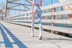 movimentar-se A mulher bonita está correndo através da ponte imagens de stock royalty free