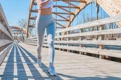 movimentar-se A mulher bonita está correndo através da ponte foto de stock