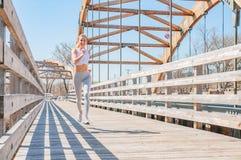 movimentar-se A mulher bonita está correndo através da ponte imagem de stock