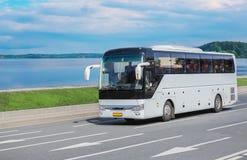Movimenti del bus turistico lungo la strada lungo la riva del lago fotografia stock