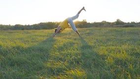 Movimenti e posizioni di pratica di yoga del giovane ad erba verde al prato Tipo sportivo che sta alla posa di yoga in natura immagini stock libere da diritti