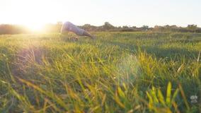 Movimenti e posizioni di pratica di yoga del giovane ad erba verde al prato Tipo sportivo che sta alla posa di yoga in natura fotografia stock libera da diritti