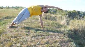 Movimenti e posizioni di pratica di yoga del tipo all'aperto Giovane che sta alla posa di yoga alla natura Atleta che fa forza fotografie stock