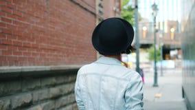 Movimenti lenti della giovane signora che camminano all'aperto poi che girano sbattere le palpebre cappello commovente archivi video