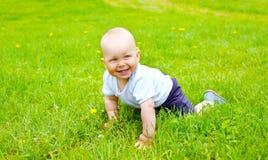 Movimenti striscianti sorridenti svegli del bambino sull'erba Fotografia Stock Libera da Diritti