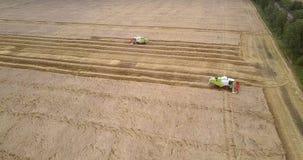 Movimento aéreo acima do campo aos tratores que recolhem a colheita video estoque