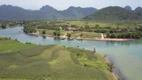Movimento acima dos campos no rio com a vila na opinião superior do banco filme