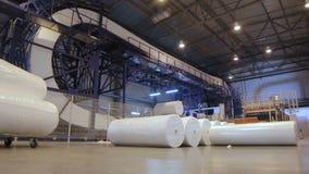 Movimento através do armazém espaçoso com o Rolls de borracha embalado filme