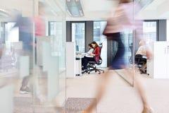 Movimento borrado da mulher de negócios que anda com os colegas que trabalham no fundo no escritório imagem de stock