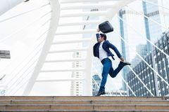 Movimento borrado do homem de negócios asiático, que guardando a pasta e saltando na cidade ao comemorado seu negócio bem sucedid imagem de stock