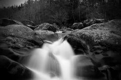 Movimento borrado Greyscale e fotografia lenta de Waterscape do obturador de uma queda da água sobre grandes pedras imagens de stock