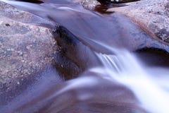Movimento borrado macro e fotografia lenta da queda da água da velocidade do obturador sobre a pedra imagem de stock royalty free