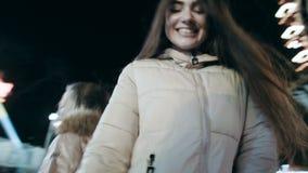 Movimento circular da câmera durante a dança de duas moças Dança bonita de duas jovens mulheres na noite no video estoque