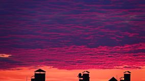Movimento cor-de-rosa das nuvens do por do sol sobre telhados da cidade filme