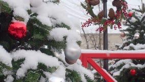 Movimento da câmera da parte inferior a cobrir com foco nas bolas coloridas que penduram na árvore de Natal coberta com a neve e