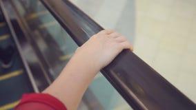 Movimento da mão do ` s da mulher nos corrimão da escada rolante 4k, lento-movimento, close-up vídeos de arquivo