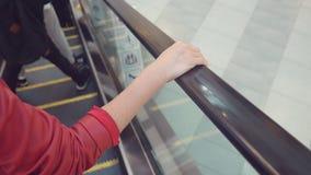 Movimento da mão do ` s da mulher nos corrimão da escada rolante 4k, lento-movimento, close-up video estoque