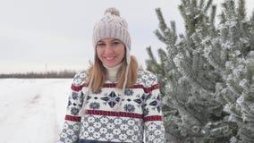Movimento da mulher bonita de sorriso que anda no inverno na neve ao longo da árvore de abeto filme