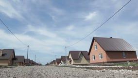 Movimento da vista inferior ao longo da estrada entre casas do tijolo vídeos de arquivo