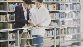Movimento da zorra dos estudantes com os livros que preparam-se ao exame na biblioteca filme