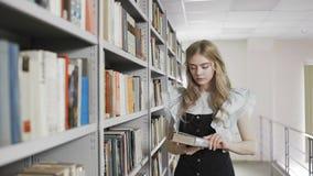 Movimento da zorra da mulher loura do estudante que toma o livro da prateleira na biblioteca da universidade video estoque