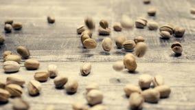 MOVIMENTO de SLOQ dos pistaches no fundo de madeira de queda filme