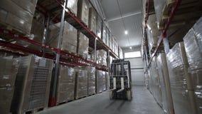 Movimento dei carrelli elevatori a forcale fra i grandi scaffali del metallo ad un magazzino moderno stock footage