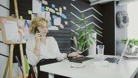 Movimento del carrello del progettista femminile attraente Talking sul telefono cellulare archivi video