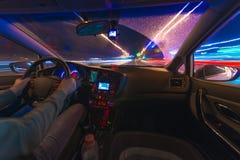 Movimento dell'automobile alla notte ad una vista di velocità dalla strada interna e brillante con le luci con un'automobile all' Fotografia Stock Libera da Diritti