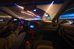Movimento dell'automobile alla notte ad una vista di velocità dalla strada interna e brillante con le luci con un'automobile all' Immagini Stock Libere da Diritti