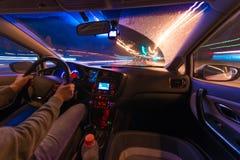 Movimento dell'automobile alla notte ad una vista di velocità dalla strada interna e brillante con le luci con un'automobile all' Fotografie Stock Libere da Diritti