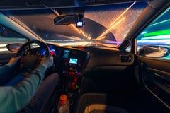 Movimento dell'automobile alla notte ad una vista di velocità dalla strada interna e brillante con le luci con un'automobile all' Immagine Stock Libera da Diritti