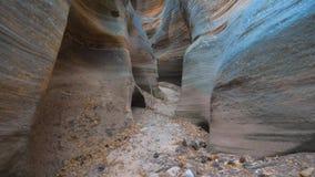 Movimento della macchina fotografica lungo la gola asciutta del fiume rocce su liscie ed ondulate del canyon Fotografie Stock