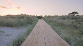 Movimento della macchina fotografica lungo un decking di legno che conduce lungo le dune di sabbia archivi video