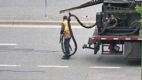 Movimento do asfalto de enchimento do trabalhador na estrada após a estação chovendo grande filme