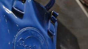 Movimento do close up após a bolsa de brilho azul do tipo na loja video estoque