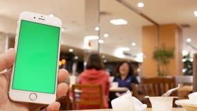 Movimento do homem que guarda o telefone de tela verde com os povos do borrão que comem o alimento e a conversa