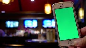 Movimento do homem que guarda o telefone de tela verde com o trabalhador do borrão que trabalha na barra filme