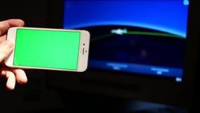 Movimento do homem que guarda o telefone esperto da tela verde com informação do voo vídeos de arquivo