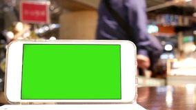 Movimento do telefone de tela verde com os povos do borrão que compram e que descansam video estoque