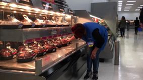 Movimento do trabalhador que põe a galinha temperado quente sobre a cremalheira do forno da exposição para a venda vídeos de arquivo
