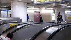 Movimento dos assinantes que tomam a escada rolante para ir à plataforma do skytrain durante horas de ponta vídeos de arquivo