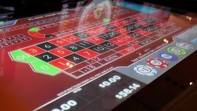 Movimento dos povos que jogam a roleta do casino na m?quina com a bola de giro da reflex?o na tela dentro do casino video estoque