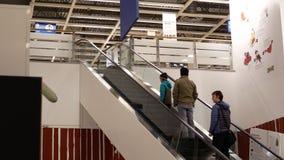 Movimento dos povos que tomam a escada rolante dentro da loja de Ikea vídeos de arquivo