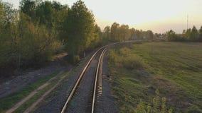 Movimento em uma estrada de ferro single-track nos raios do sol de ajuste filme