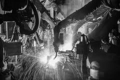 Movimento em uma fábrica do carro, black&white dos robôs de soldadura Fotografia de Stock Royalty Free