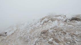 Movimento em uma inclinação de montanha rochoso As rochas e a grama são cobertas com a geada video estoque
