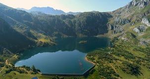 Movimento inverso de uma vista aérea de um lago cercado por montanhas vídeos de arquivo