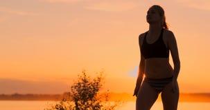 MOVIMENTO LENTO, BAIXO ÂNGULO, FIM ACIMA, ALARGAMENTO DO SOL: Menina atlética que joga saltos do voleibol de praia no ar e nas gr vídeos de arquivo