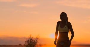 MOVIMENTO LENTO, BAIXO ÂNGULO, FIM ACIMA, ALARGAMENTO DO SOL: Menina atlética que joga saltos do voleibol de praia no ar e nas gr video estoque